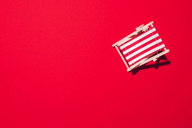 Deck chair with hard shadow on red paper background.