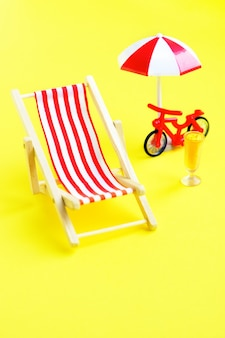 Deck chair with umbrella and bicycle on yellow.