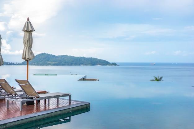 Шезлонги и пейзажный бассейн с прекрасным видом на море.