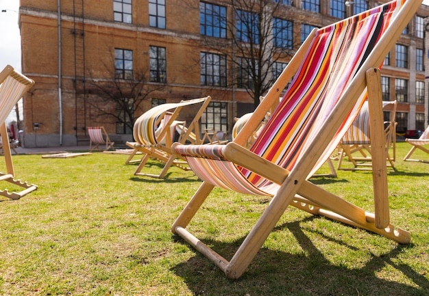 Deck chairs on a lawn in an apartment complex with their brightly colored canvas seats blowing in the wind