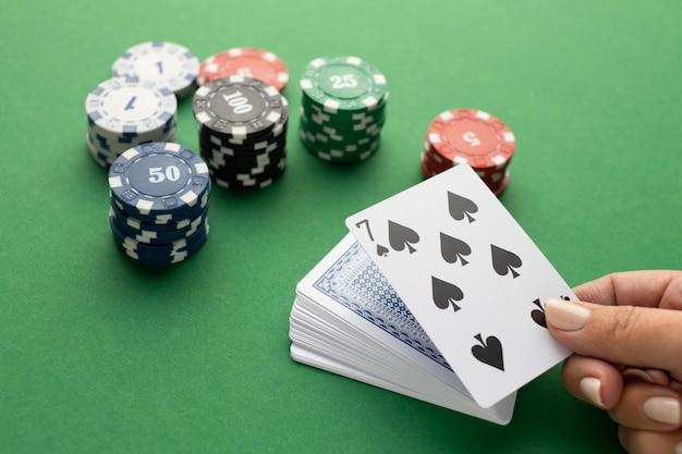 Колода карт и жетоны казино на зеленом фоне