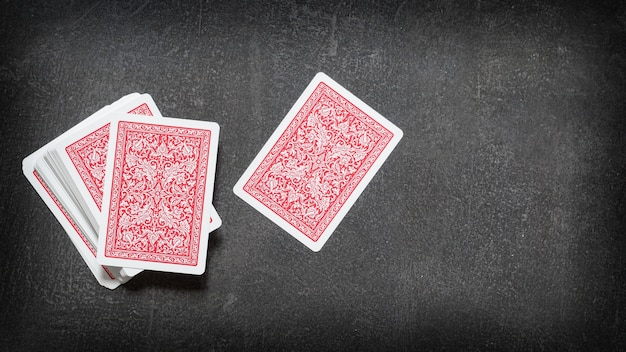 Deck of playing cards and one card separately face down on a black table