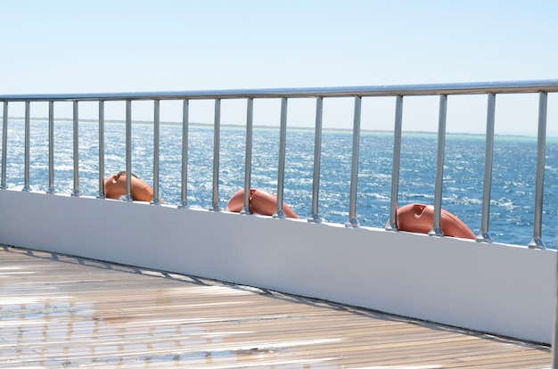 Deck on the stern of the yacht on a sunny day and beautiful blue sea water.