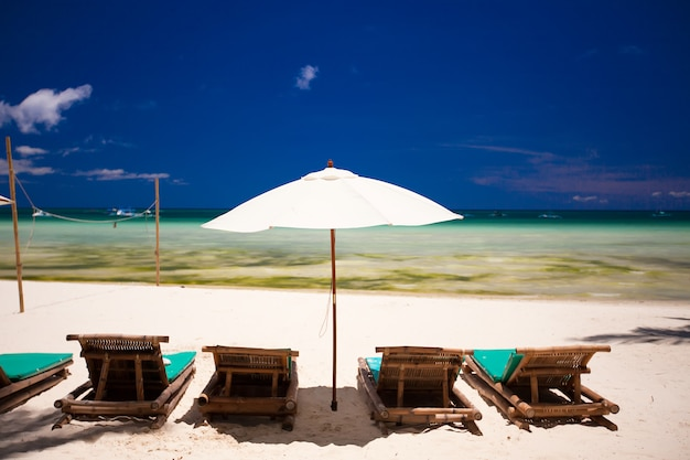 Deckchairs and parasol on white sand beach facing the lagoon