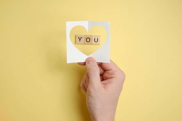 Declaration of love. hand holds abstract paper heart over wooden squares with the word - you. paper yellow background.