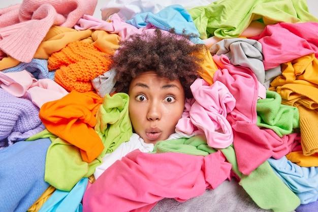Decluttering, pulizie di primavera di seconda mano, fast fashion e organizzazione della vita. la donna afroamericana sbalordita con i capelli ricci guarda attraverso un grande mucchio di vestiti colorati mette le cose in ordine nell'armadio