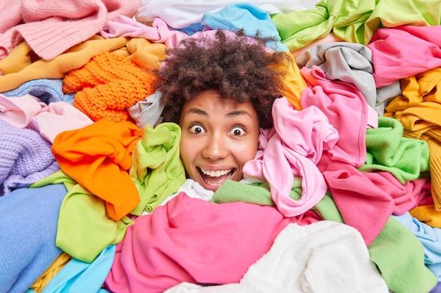 Concetto di decluttering e riordino. la donna afroamericana riccia positiva impressionata ordina i vestiti nell'armadio coperto con una pila di vestiti multicolori organizza l'armadio rivende gli abiti usati