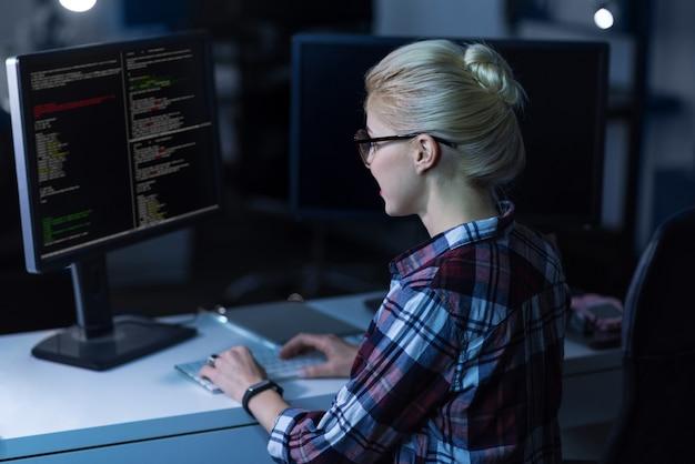 Расшифровка важной информации. в восторге участвовал опытный хакер, сидящий в темной освещенной комнате и использующий компьютеры, концентрируясь и просматривая интернет.