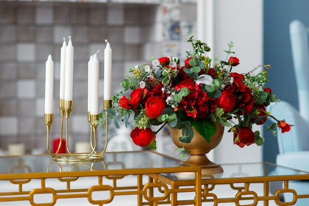 Decor of candles in candlestick and vase with flowers..