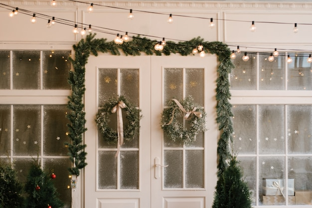 The decor of christmas and new year. beautiful facade decorated with wreaths of spruce, selective focus
