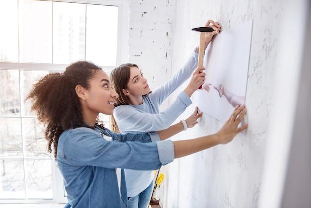 Ценители декора. веселые подруги вместе протягивают картину на стене, одна из девушек держит картину, а другая забивает гвоздь