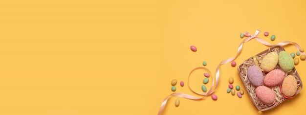 木製のickerのバスケットと甘いお菓子の装飾卵