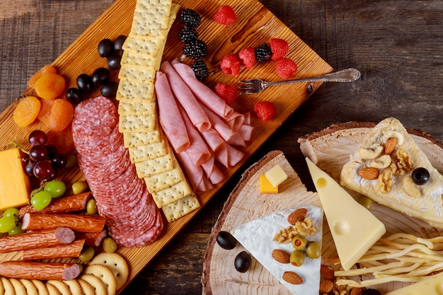 Decor fresh cheese and meat crackers, green olives, nuts and berries on wooden gray boards
