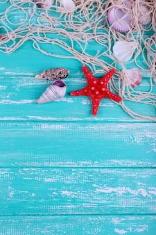 青い木製のテーブルの上の貝殻のクローズアップの装飾