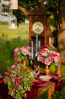 Decor of wedding table. clock and flowers on the wooden table. outdoor wedding ceremony.