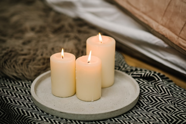 촛불 장식. 아늑한 침대보의 배경, 편안함과 아늑함의 개념에 촛불이있는 인테리어의 정물 가정 분위기. 가정 장식의 겨울 요소. 확대.