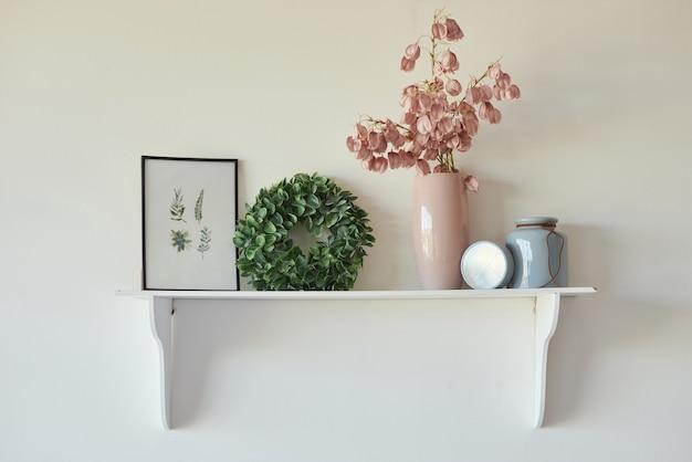 액자 그림과 꽃병에 꽃이 있는 흰색 벽의 장식 선반에 장식하세요