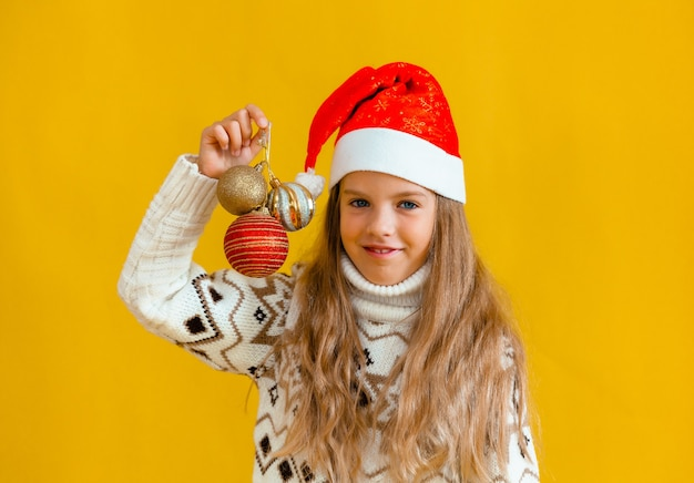 Украсить елку. маленькая блондинка девочка держит рождественские шары. ребенок в новогодней шапке держит новогодние украшения.