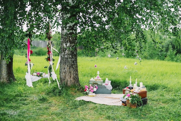 Decorated area for the wedding with swings, flowers, and decorations outdoors under a tree
