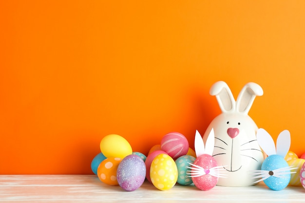 Decorated bunny and easter eggs on table against color background