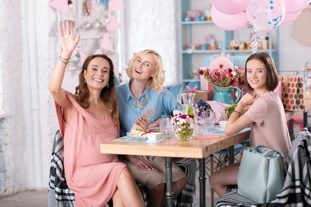 飾られたカフェ。たくさんの風船とプレゼントのある素敵な装飾が施されたカフェでベビーシャワーを祝う3人の女性