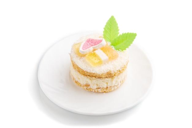 白で隔離のミルクとココナッツクリームで飾られたケーキ