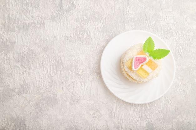 灰色のコンクリートにミルクとココナッツクリームで飾られたケーキ