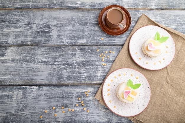 회색 나무에 커피 한잔과 함께 우유와 코코넛 크림으로 장식 된 케이크