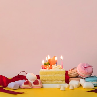 Decorated cakes with candies; marshmallow and macarons on yellow desk