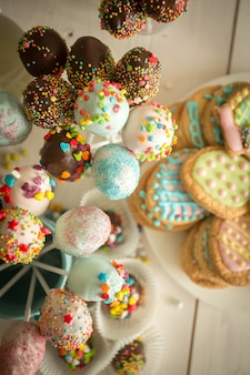 Decorated candies, cake pops and cookies on white wooden desk