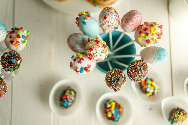 Decorated candies and cake pops on wooden boards