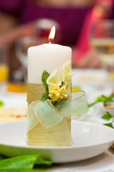 Decorated candle on the wedding table, slavic ritual of lighting the hearth.