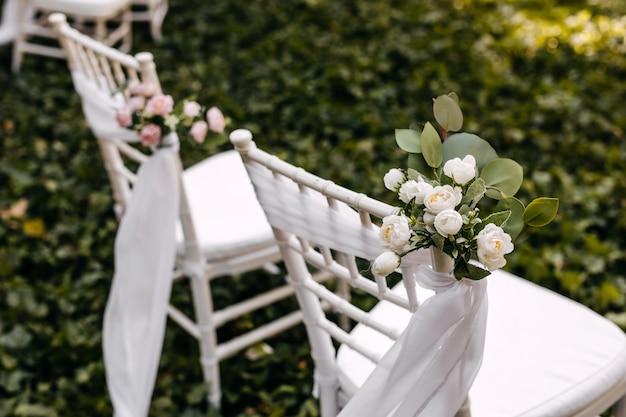 Украшенные стулья на свадебной церемонии на открытом воздухе