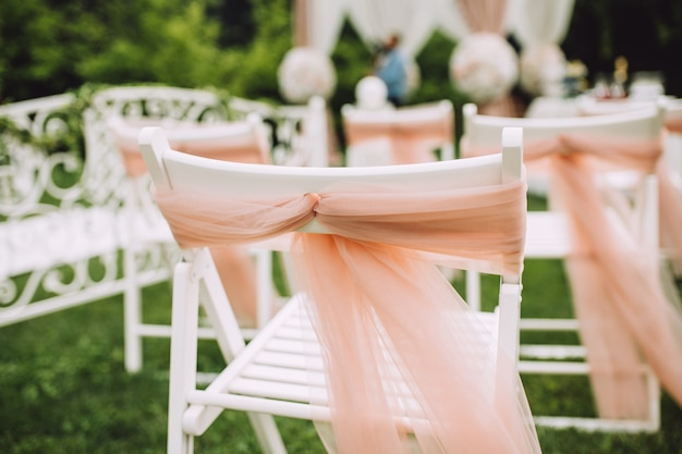 Decorated chairs stand on the grass. wedding arch made of cloth and white and pink flowers on a green natural surface.