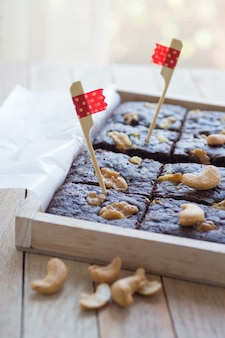 Decorated chocolate brownies with walnut in wood box