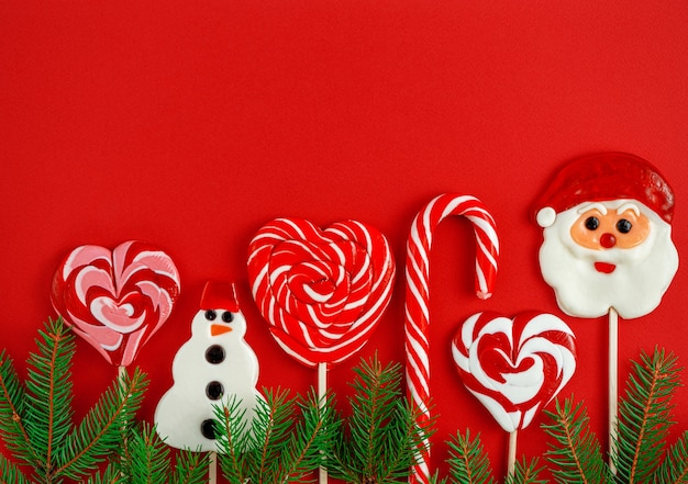 Decorated christmas candies on red background