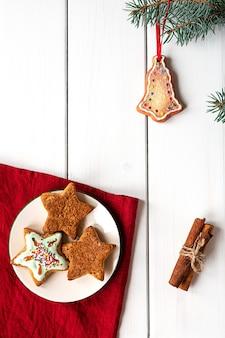 Украшенное рождественское печенье на белом деревянном фоне