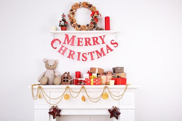 白い壁の背景に「メリークリスマス」の碑文と飾られたクリスマスの暖炉