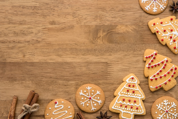 Decorated christmas gingerbread cookies on wood background