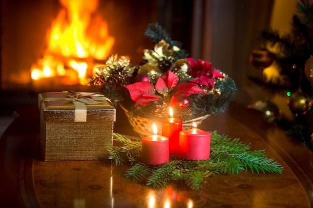燃える暖炉のあるリビングルームの装飾されたクリスマステーブル