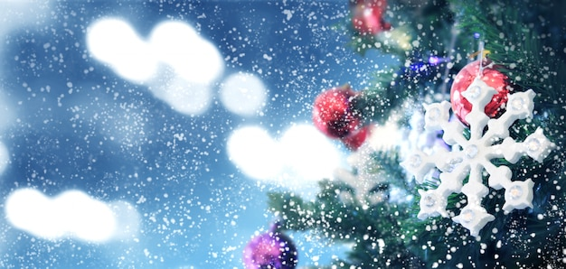 Decorated christmas tree on  blurred background. pine cone and snow flakes