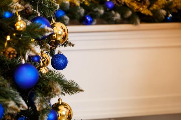 飾られたクリスマスツリーのクローズアップ。ブルーとゴールドのボールとガーランドライト。木の上のクリスマスボール。冬休み正月・クリスマス