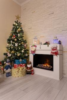 燃える暖炉の近くの飾られたクリスマスツリー、ギフト、クリスマスの装飾