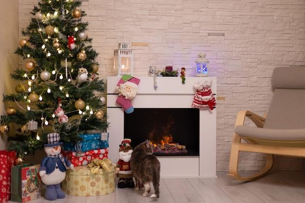 Украшенная елка, подарки в коробках, кошка у горящего камина. новый год, рождество. выборочный фокус.