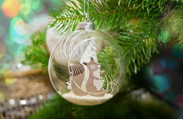 Decorated christmas tree and hanging small ball with funny squirrel toy inside