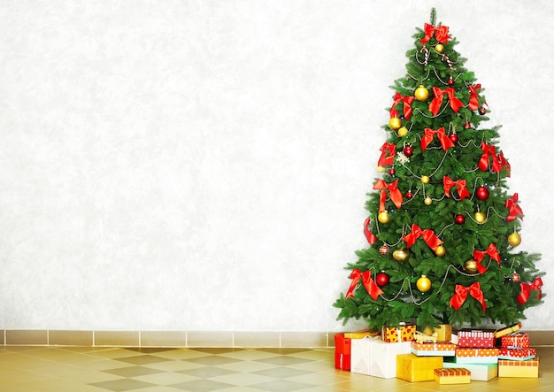 Decorated christmas tree on light wall surface