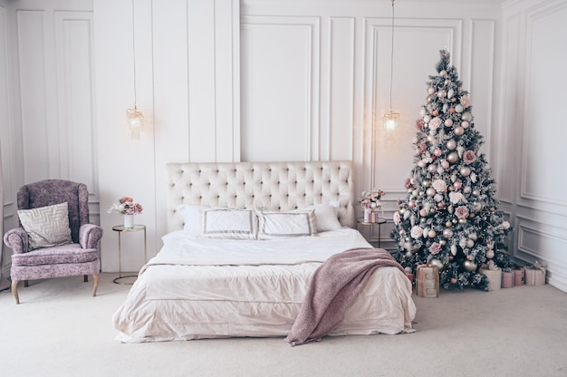 Decorated christmas tree in white classic bedroom interior