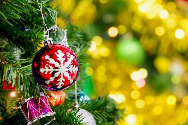 抽象的なゴールドのボケ味の明るい背景で飾られたクリスマスツリー