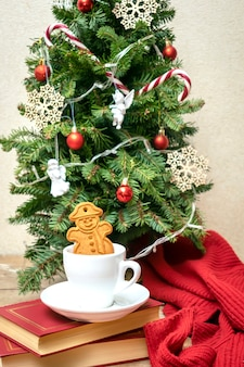 Decorated christmas tree with cup of tea coffee and ginger cookies, balls, snowflakes, candy canes, angels, lights garland, festive decor. xmas, new year decorations. winter holiday concept.