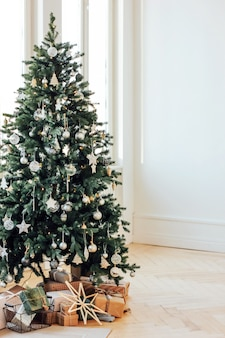 Decorated christmas tree with gifts in bright living room, scand